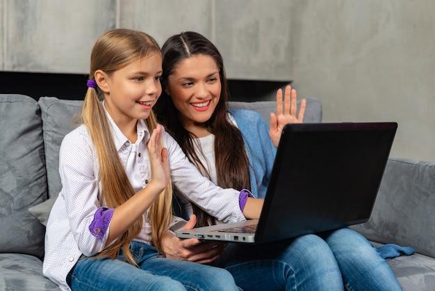 La bella madre e sua figlia sta avendo chiamata di skype sul computer portatile mentre si siedono a casa Foto Premium