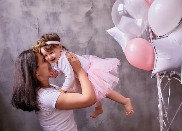 La bella mamma tiene in braccio la tenera figlia in piedi nella stanza Foto Gratuite