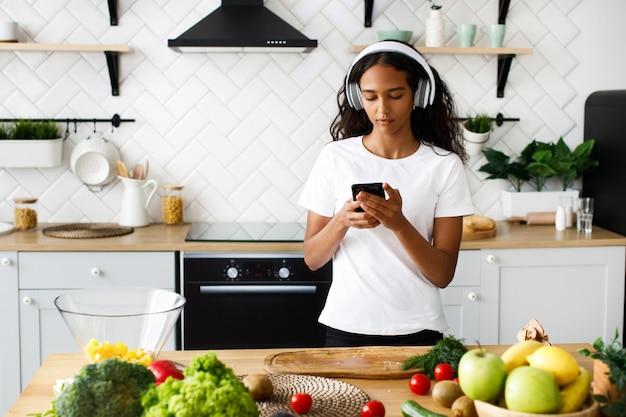 La bella mulatta tiene in mano uno smartphone, con grandi cuffie senza fili, vestita con una maglietta bianca, vicino al tavolo con verdure fresche Foto Gratuite
