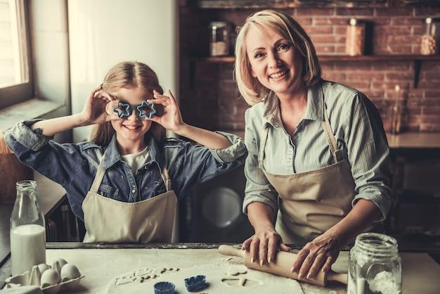La bella nonna e la nipote stanno tagliando i biscotti. Foto Premium