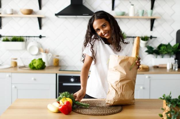 La bella ragazza afro disimballa i prodotti da un supermercato e parla al telefono Foto Gratuite