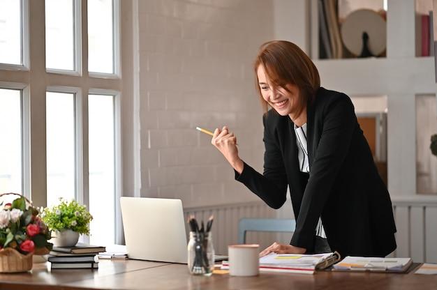 La bella ragazza asiatica celebra riuscito con le armi su che celebra la vittoria sul posto di lavoro dell'ufficio. Foto Premium