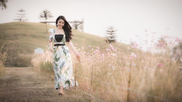 La bella ragazza asiatica delle donne che cammina e che sorride si rilassa nell'annata di stile dell'immagine del fiore del parco Foto Premium