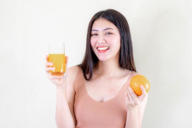 La bella ragazza asiatica di bellezza della ragazza di bellezza ritiene felice il succo d'arancia bevente per buona salute di mattina Foto Gratuite