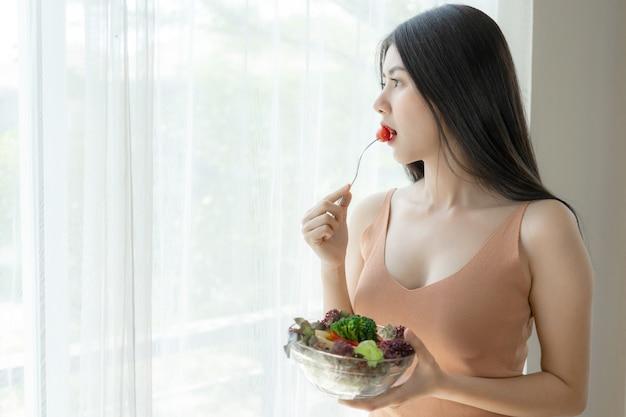 La bella ragazza asiatica di bellezza della ragazza di tatto felice mangia l'insalata fresca dell'alimento di dieta per buona salute di mattina Foto Gratuite