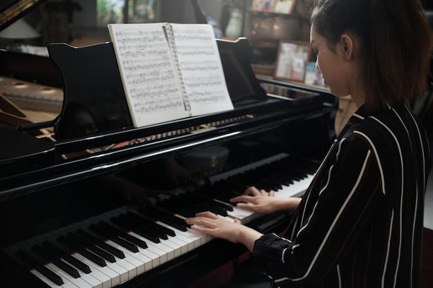 La bella ragazza asiatica impara a suonare il piano. Foto Premium