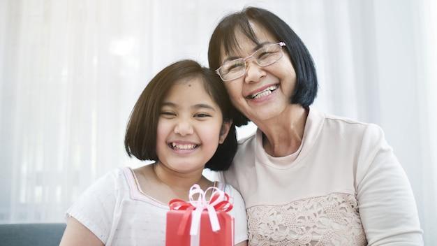 La bella ragazza asiatica offre una scatola regalo spaziale a sua nonna Foto Premium