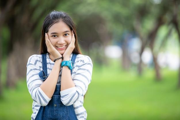 La bella ragazza asiatica sorridente all'albero sul parco di estate per si rilassa il tempo Foto Premium