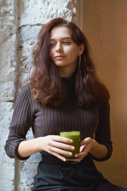 La bella ragazza astuta alla moda alla moda seria sta sedendosi nel caffè e sta bevendo il frullato verde Foto Premium