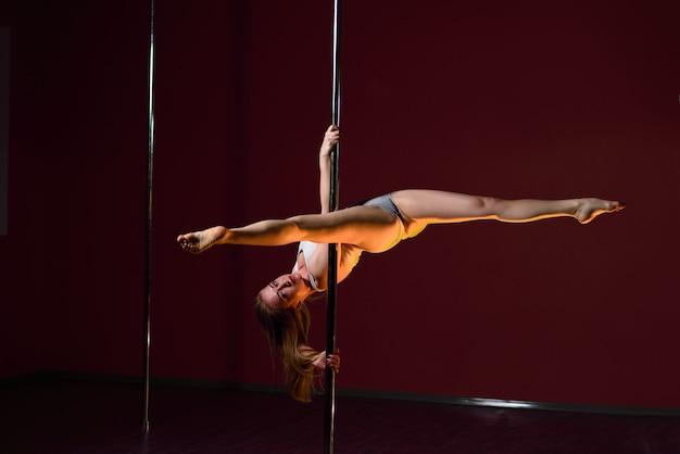La bella ragazza balla vicino al palo. Foto Premium