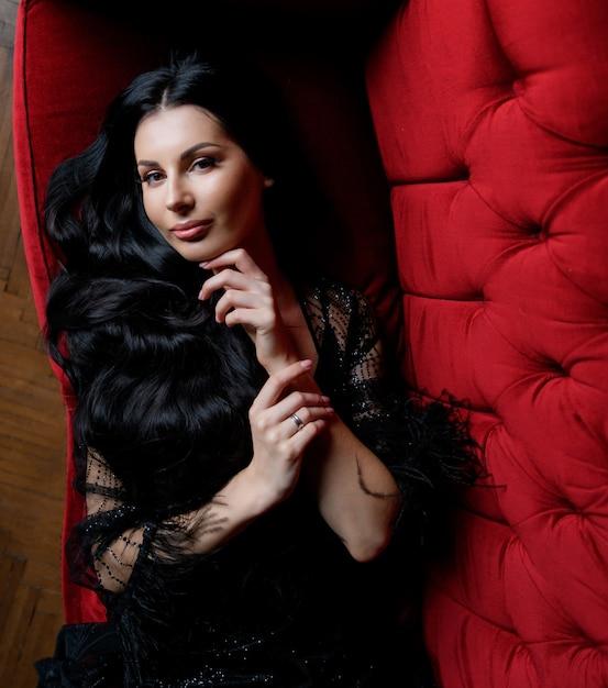 La bella ragazza caucasica castana dai capelli lunghi sta guardando diritto e sta trovandosi sul sofà rosso Foto Gratuite