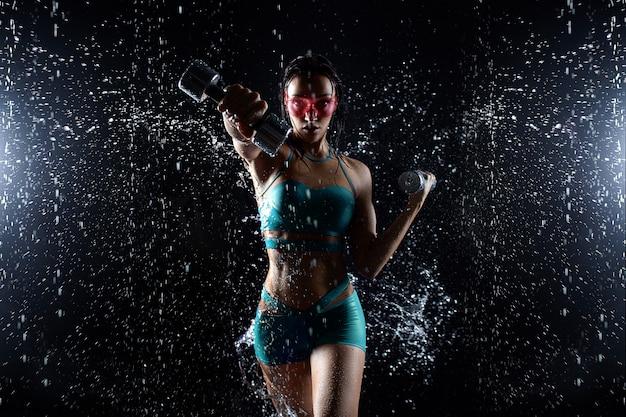 La bella ragazza in abiti sportivi posa con le teste di legno nello studio dell'acqua Foto Premium