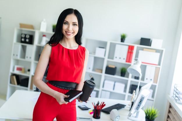 La bella ragazza in un vestito rosso sta stando nell'ufficio e sta tenendo un taccuino e un bicchiere di caffè. Foto Premium