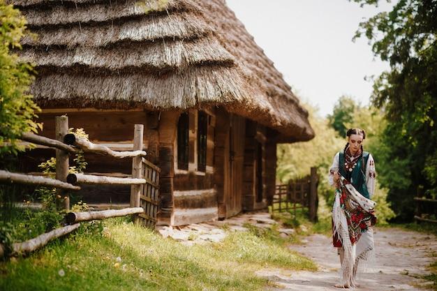 La bella ragazza in un vestito tradizionale colorato cammina intorno al villaggio Foto Gratuite
