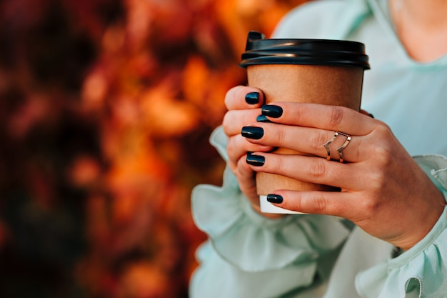 La bella ragazza in via di autunno tiene una tazza con una bevanda calda in sue mani Foto Premium