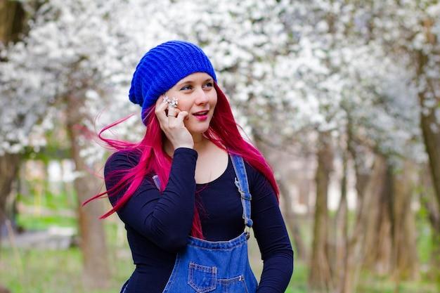 La bella ragazza incinta luminosa cammina nel parco della molla di fioritura Foto Premium