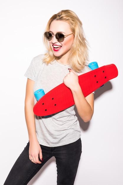 La bella ragazza pattinatrice blodnie sorridente in occhiali da sole brillanti rimane davanti al muro bianco Foto Gratuite