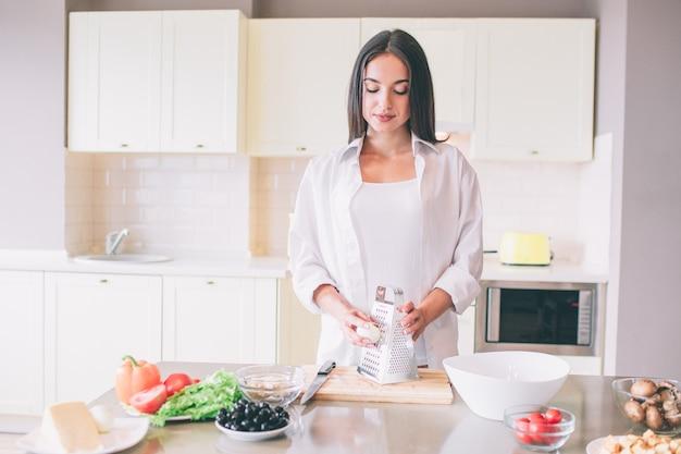 La bella ragazza sta a tabel e tiene l'uovo sodo vicino alla grattugia. lei guarda in basso. la ragazza è calma ma concentrata. Foto Premium