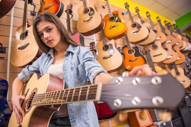 La bella ragazza sta suonando la chitarra in un negozio di musica. Foto Premium
