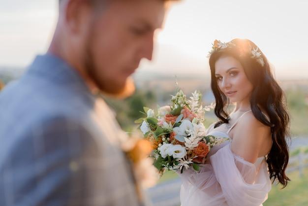 La bella sposa castana con lo sguardo sexy sta tenendo il mazzo grazioso di nozze fatto dei eustomas e della pianta freschi sul tramonto e sullo sposo vago Foto Gratuite