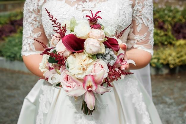 La bella sposa sta tenendo un mazzo variopinto di nozze. bellezza di fiori colorati Foto Premium