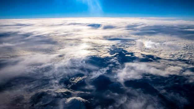 La bella vista delle nuvole e della montagna sotto un chiaro cielo ha sparato da un aeroplano Foto Gratuite