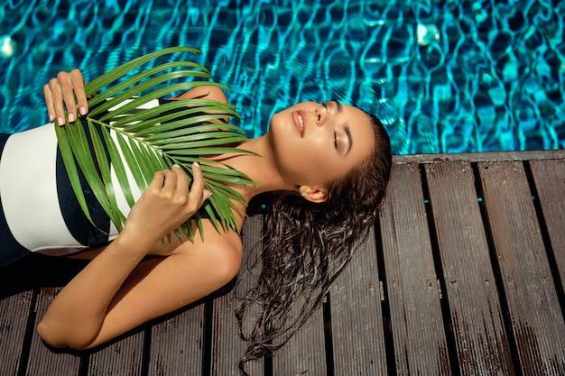 La bellezza abbronzata con i capelli bagnati si trova vicino alla piscina con una foglia verde. spa e concetto di relax Foto Premium