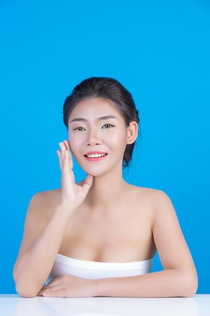 La bellezza delle donne con immagini perfette di salute della pelle toccando il suo viso e sorridendo come una spa per coccolarla. blu Foto Gratuite