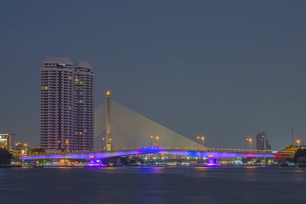 La bellezza delle luci colorate sul ponte di pinklao e le auto che guidano di notte sul fiume chao phraya Foto Premium