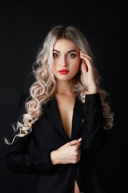 La bionda sexy con capelli ricci lunghi posa in giacca nera in uno studio scuro Foto Gratuite