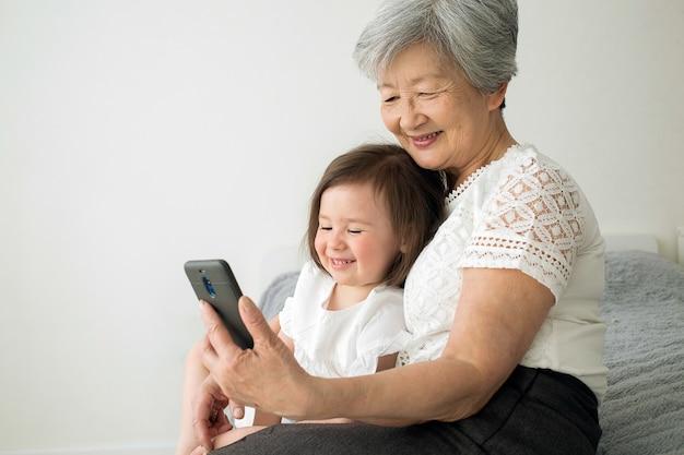 La bisnonna si siede con la pronipote e guarda nello smartphone. Foto Premium
