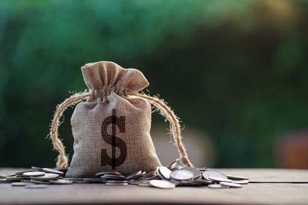 La borsa dei soldi su legno con le monete impila alla luce di mattina. Foto Premium