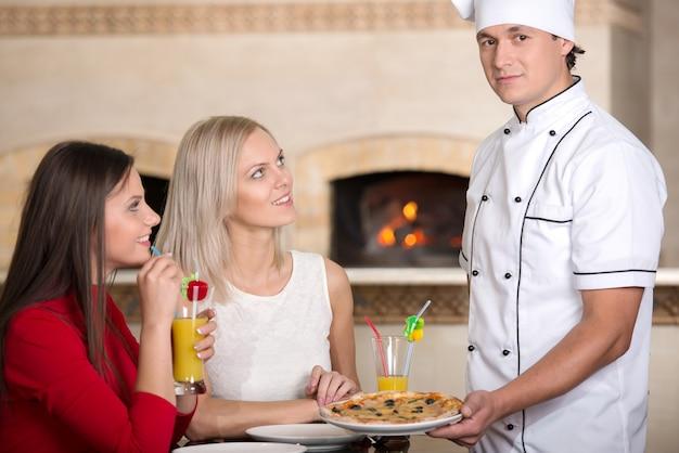 La cameriera sta dando la pizza a una donna sorridente in pizzeria. Foto Premium