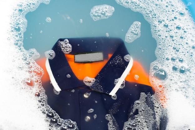 La camicia polo si impregna in dissoluzione di acqua detergente in polvere. Foto Premium
