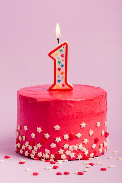 La candela numero uno accesa sulla torta rossa con stella spruzza su sfondo viola Foto Gratuite