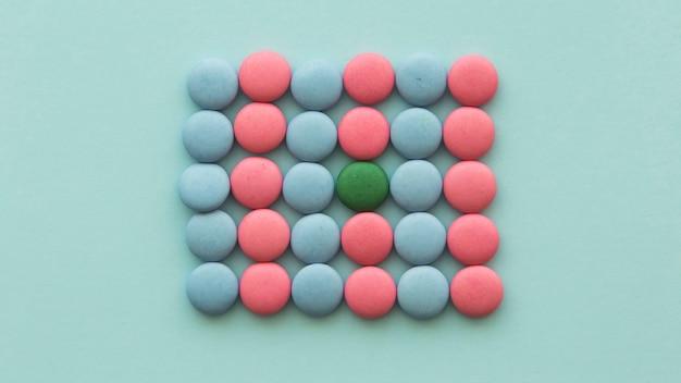 La caramella verde ha sistemato nelle caramelle rosa e blu su fondo colorato Foto Gratuite