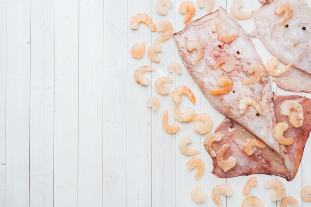 La carcassa cruda di calamari e gamberi con spezie e limone è pronta per la cottura sul tavolo. Foto Premium