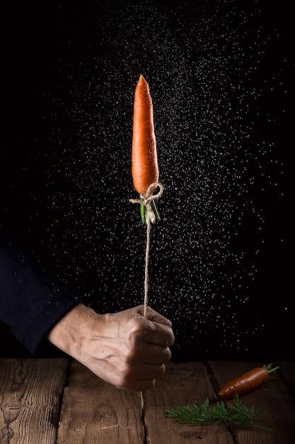 La carota si lancia come un razzo su nero Foto Premium