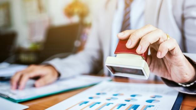 La carta del documento del bollo della mano dell'uomo di affari per approva. Foto Premium