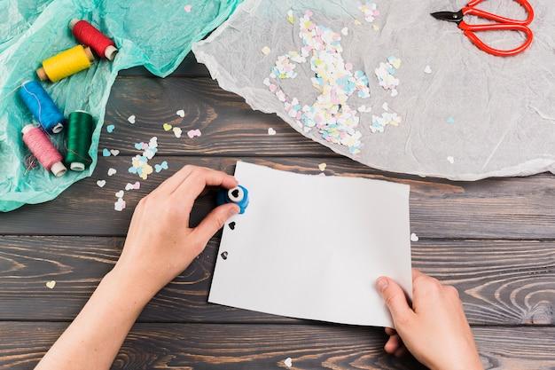 La carta femminile di taglio della mano con la macchina della perforazione di forma del cuore vicino avvolge il filo e forbice sopra la tavola Foto Gratuite