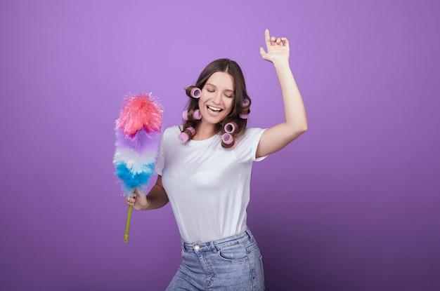 La casalinga in bigodini canta canzoni e balla mentre pulisce. Foto Premium