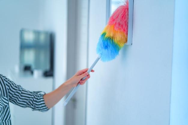 La casalinga pulisce la polvere con una spazzola per la polvere durante le pulizie di primavera a casa. faccende domestiche e pulizie Foto Premium