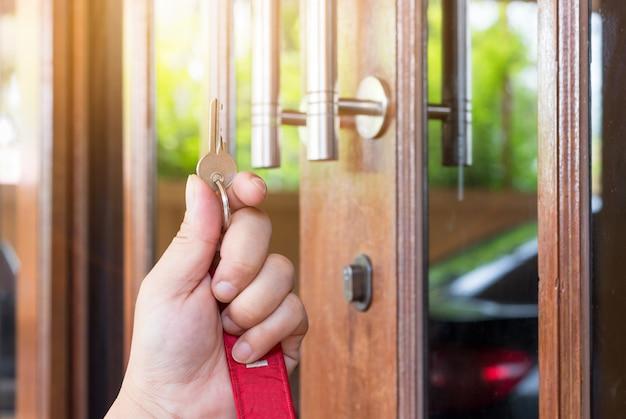 La chiave a portata di mano delle persone apre la porta verso l'interno, porta esterna aperta mettendo nella porta d'ingresso Foto Premium