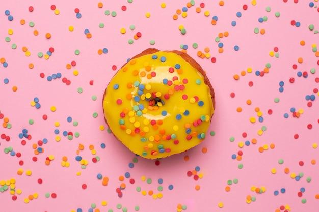 La ciambella gialla dolce con spruzza su una disposizione piana del fondo rosa Foto Premium