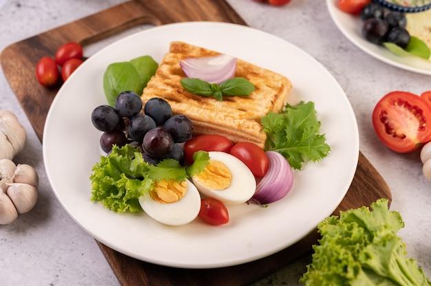 La colazione comprende pane, uova sode, condimento per insalata di uva nera, pomodori e cipolle affettate. Foto Gratuite
