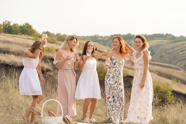 La compagnia di splendide amiche si diverte e si gode un picnic estivo, ballando e bevendo alcolici. concetto di persone. Foto Premium
