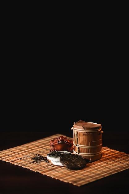La composizione del tè del puer con rospo dorato su una stuoia di bambù. sfondo nero. Foto Gratuite