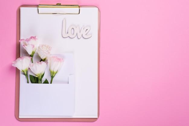 La composizione minima con un eustoma fiorisce in una busta sulla lavagna per appunti su un fondo rosa, vista superiore. cartolina d'auguri di san valentino, compleanno, madre o matrimonio Foto Premium