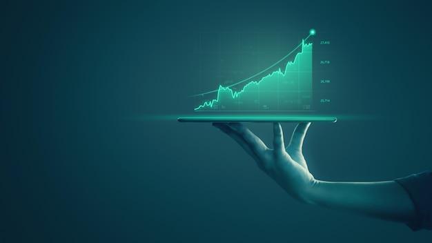 La compressa della tenuta dell'uomo d'affari e la rappresentazione dei grafici olografici e delle statistiche del mercato azionario guadagnano i profitti. Foto Premium