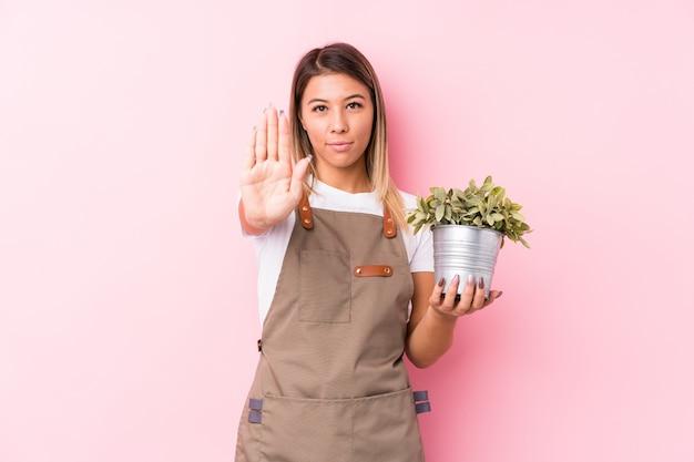La condizione isolata giovane donna caucasica del giardiniere con la mano tesa che mostra il fanale di arresto, impedendovi. Foto Premium